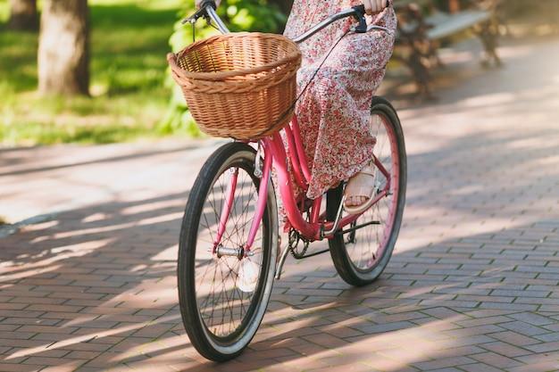 Gros plan photo recadrée d'une jeune femme en longue robe à fleurs rose chevauchant un vélo vintage avec panier pour les achats, de la nourriture ou des fleurs à l'extérieur, des roues, des loisirs féminins au printemps ou dans un parc d'été.