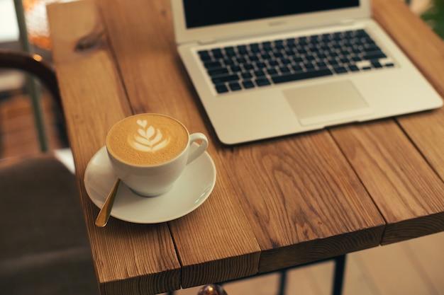Gros plan photo d'une table en bois avec une tasse de café sur une assiette. ordinateur portable moderne sur le fond