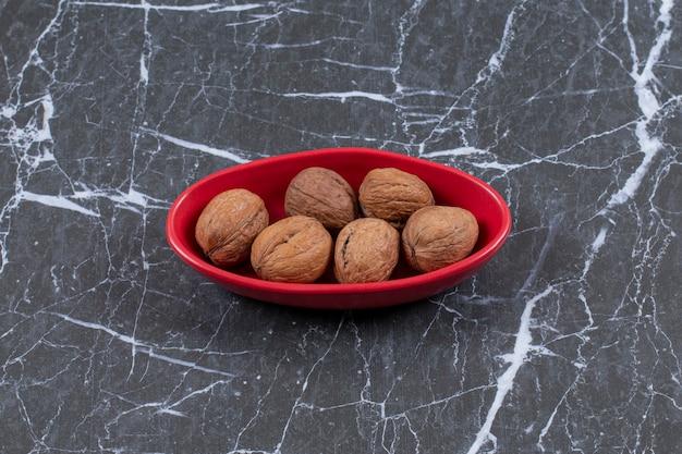 Gros plan photo tas de noix dans un bol rouge