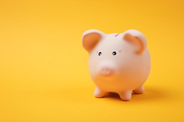 Gros plan photo de tirelire rose isolé sur fond de mur jaune vif. accumulation d'argent, investissement, services bancaires ou commerciaux, concept de richesse. copiez la maquette publicitaire de l'espace.