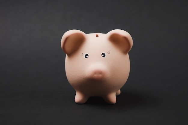 Gros plan photo de tirelire rose isolé sur fond de mur noir. accumulation d'argent, investissement, services bancaires ou commerciaux, concept de richesse. copiez la maquette publicitaire de l'espace.