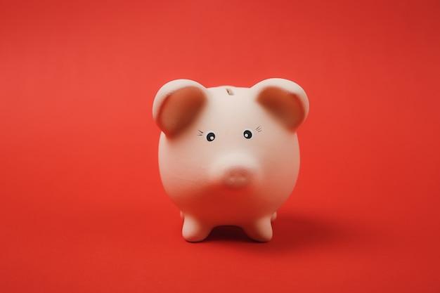 Gros plan photo de tirelire rose isolé sur fond de mur rouge vif. accumulation d'argent, investissement, services bancaires ou commerciaux, concept de richesse. copiez la maquette publicitaire de l'espace.