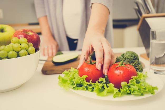 Gros plan photo tonique d'une femme cueillant des tomates fraîches de la table dans la cuisine