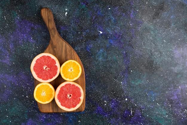 Gros plan photo de tranches de pamplemousse et d'orange sur une planche à découper en bois.