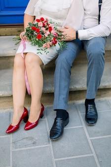 Gros plan sur une photo verticale recadrée des jambes d'un couple d'âge mûr, d'un homme et d'une femme en costume et robe élégants, assis sur des escaliers en pierre vintage avec bouquet de fleurs, à l'extérieur dans la rue de la ville