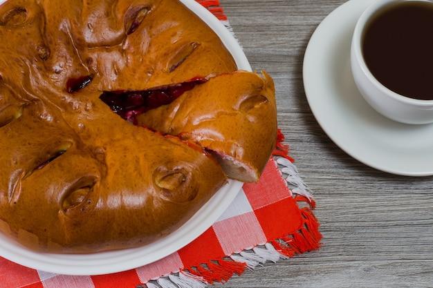 Gros plan photo vue de dessus d'une délicieuse tarte aux cerises maison et d'une tasse de thé sur une table en bois