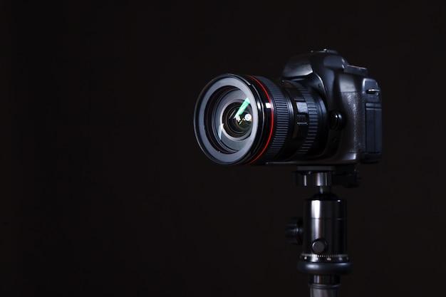 Gros plan d'une photocaméra professionnelle en studio sur fond noir. concept de séance photo