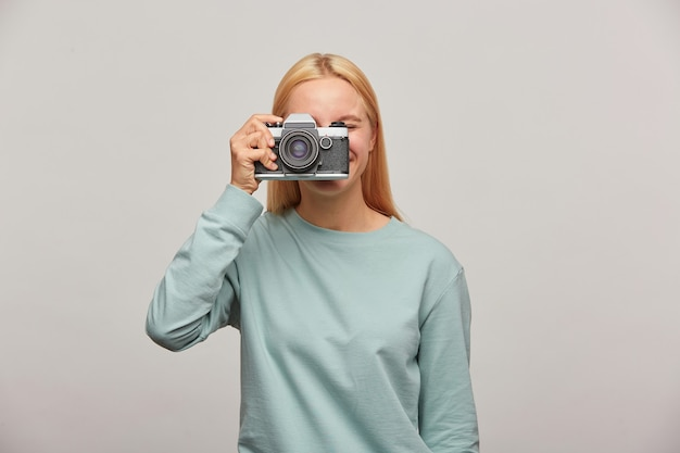 Gros plan d'un photographe couvrant son visage avec l'appareil photo vintage rétro