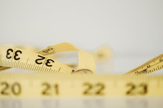 Gros plan photographie au point sélective d'un mètre jaune sur une surface blanche