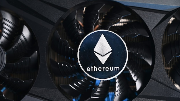Gros plan de la pièce ethereum sur une carte vidéo graphique noire. appareil commercial de crypto-monnaie. mineurs d'ethereum.