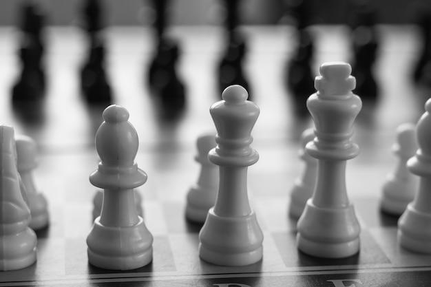 Gros plan sur des pièces blanches d'échiquier dans des concepts de stratégie de jeu d'échecs en noir et blanc