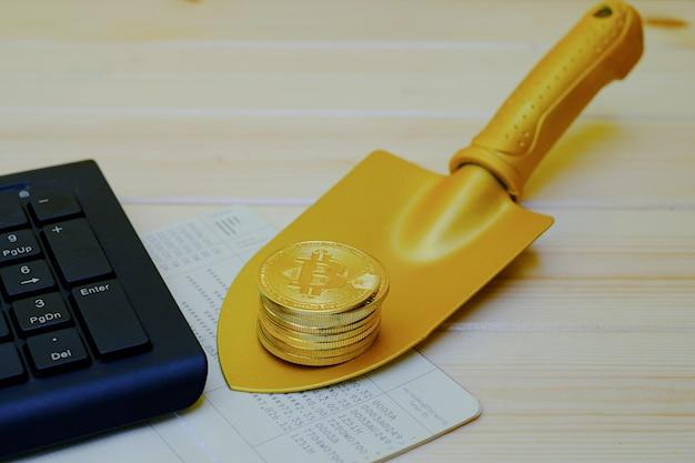 Gros plan des pièces d'or bitcoin sur livret bancaire avec une pelle d'or sur une table en bois