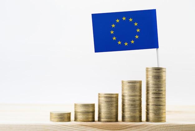 Gros plan de pièces d'or empilées de plus en plus avec le drapeau de l'union européenne