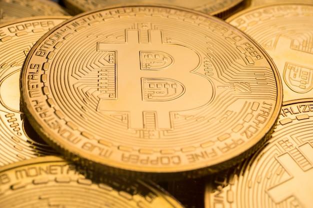 Gros plan des pièces d'or avec fond de symbole bitcoin.