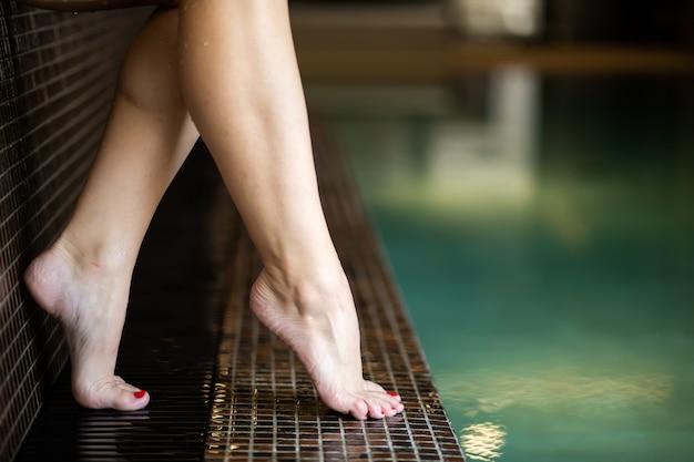 Gros plan des pieds de belle femme près d'une piscine dans un spa