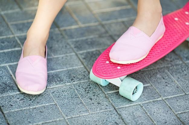 Gros plan des pieds de la belle fille en baskets roses monte sur planche de skate penny rose