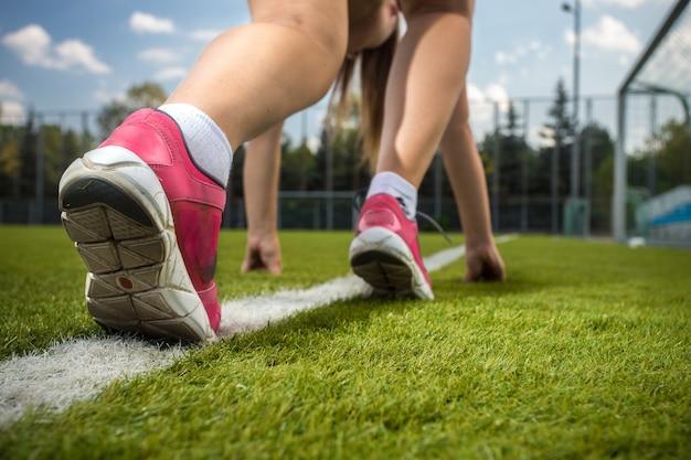 Gros plan des pieds de coureur de femme sur la ligne de départ sur l'herbe