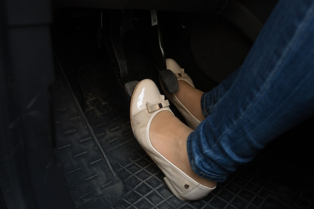 Gros plan des pieds du conducteur féminin sur les pédales de voiture