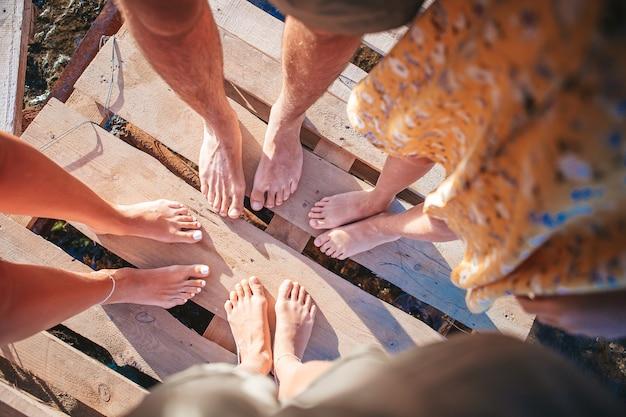 Gros plan des pieds de la famille sur la plage de sable blanc
