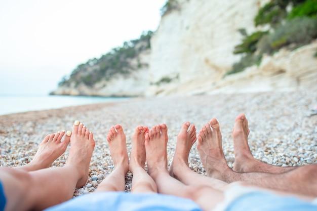 Gros plan des pieds de famille sur la plage de sable blanc