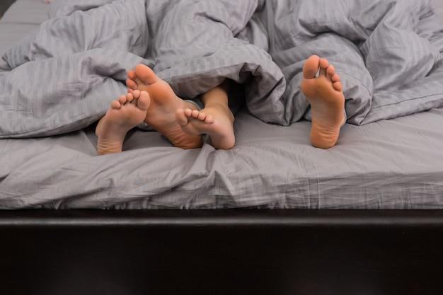 Gros plan des pieds féminins et masculins sous une couverture grise dans un lit moderne et élégant