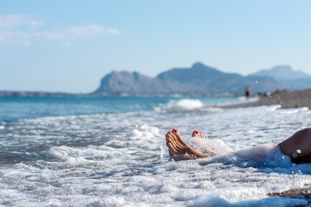 Gros plan des pieds féminins avec pédicure rose dans une mer mousseuse d'une vague sur la plage de galets de l'île de rhodes.
