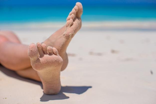Gros plan des pieds féminins sur la plage de sable blanc