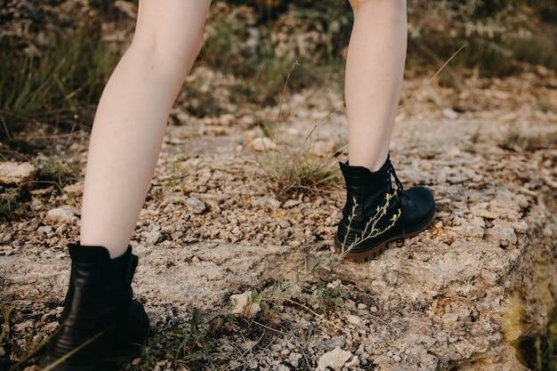 Gros plan de pieds féminins portant des bottes de randonnée en cuir noir, à l'extérieur, dans les montagnes, escalade sur des rochers.