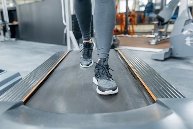 Gros plan des pieds de femme en cours d'exécution sur tapis roulant dans la salle de gym