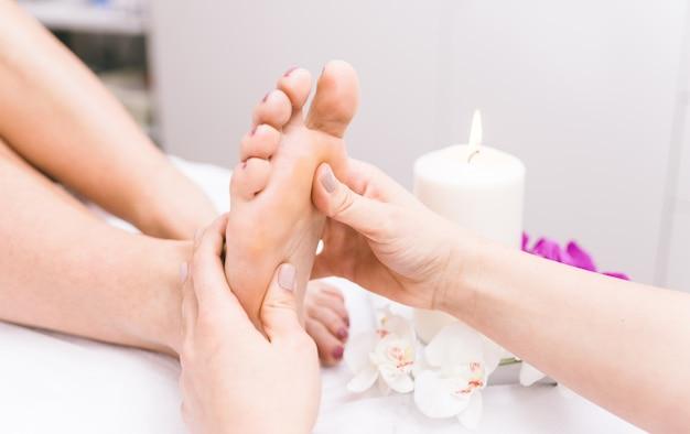 Gros plan des pieds de femme et des décorations de salon de beauté