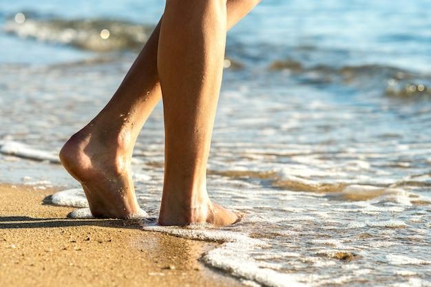 Gros plan des pieds de femme marchant pieds nus sur le sable, laissant des empreintes sur la plage dorée.