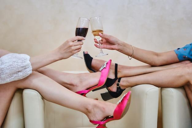 Gros plan des pieds des femmes en chaussures avec un verre de vin dans le cadre.