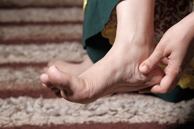 Gros plan sur les pieds des femmes et le massage des mains sur le point de blessure