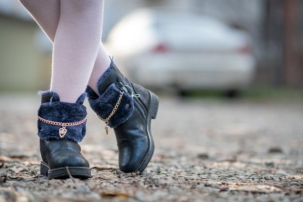 Gros plan des pieds de fille enfant en leggings roses et chaussures d'automne à la mode debout à l'extérieur par temps d'automne ensoleillé.