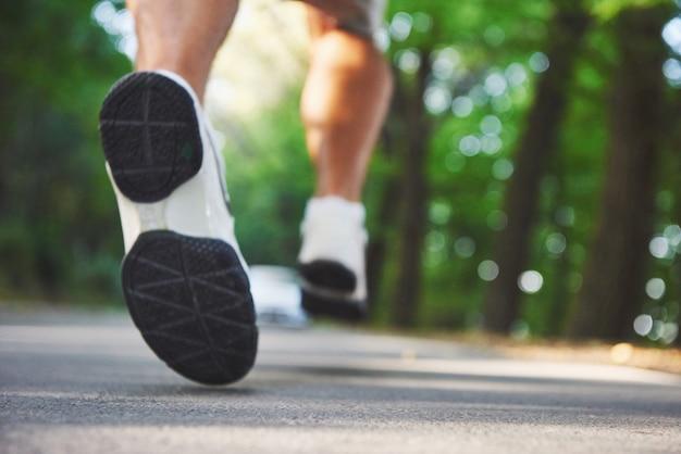 Gros plan des pieds de l'homme jeune coureur qui longe la route dans le parc.