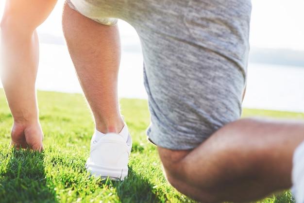 Gros plan des pieds d'un homme qui court dans l'herbe.