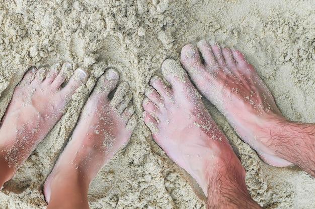 Gros plan des pieds d'un jeune couple sur la plage de sable blanc