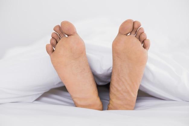 Gros plan de pieds nus au lit
