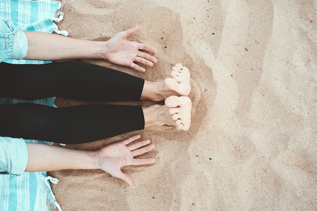 Gros plan des pieds et des paumes des femmes sur le sable avec espace de copie