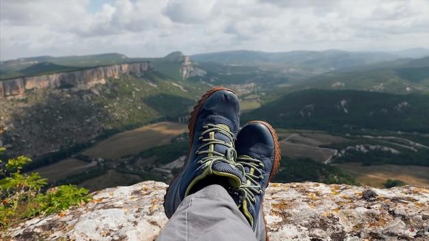 Gros plan pieds de randonneur au repos avec beau paysage de montagne