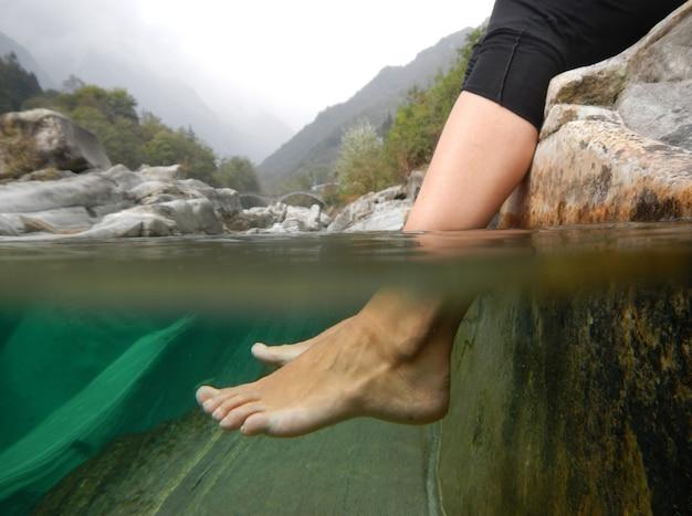 Gros plan de pieds sous l'eau dans une rivière avec des montagnes au tessin, suisse.