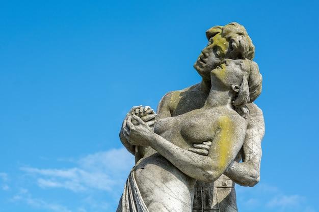 Un gros plan d'une pierre a fait une statue d'un couple avec un ciel bleu
