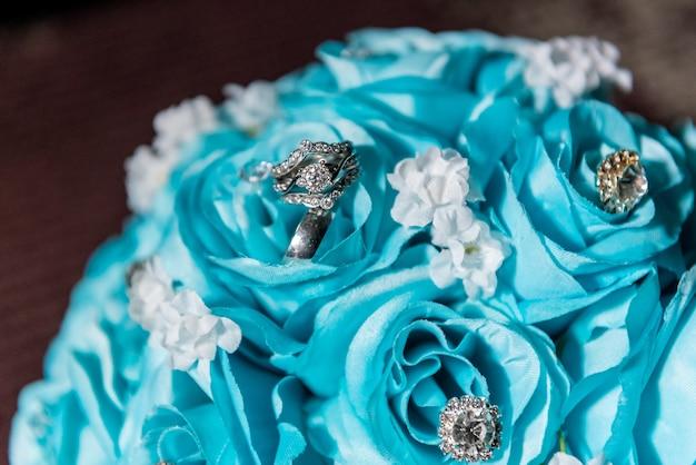 Gros plan de pierres précieuses sur un bouquet de roses bleues