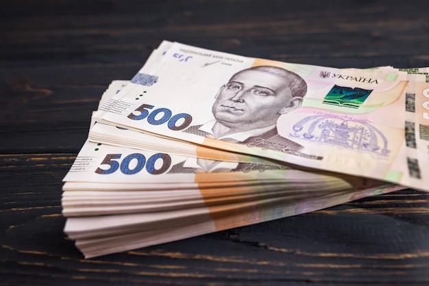 Gros plan d'une pile avec 500 hryvnia sur un fond en bois.
