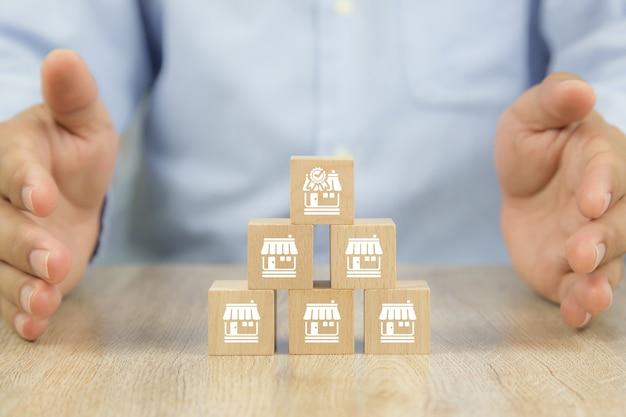 Gros plan pile de blocs de bois en pyramide avec icône de magasin de franchises
