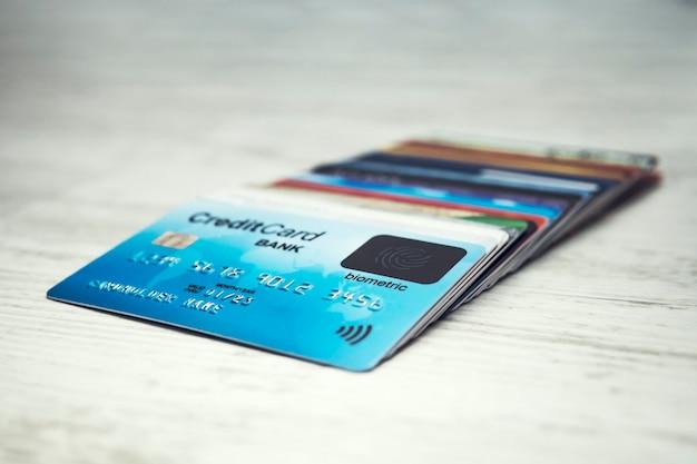 Gros plan d'une pile de cartes de crédit en ordre sur le dessus de la table blanche. de nombreuses cartes de crédit différentes avec carte biométrique sur le dessus. shopping avec la technologie de balayage biométrique. sécurité du titulaire de la carte.