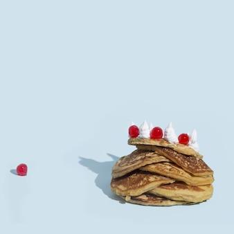 Gros plan sur une pile de crêpes avec de la crème fouettée et des bonbons sur une surface bleue