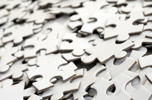 Gros plan d'une pile d'éléments inachevés d'un puzzle blanc.