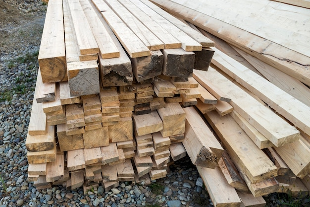Gros plan sur une pile empilée de planches de bois brut inégales brunes naturelles éclairées par un soleil éclatant. bois industriel pour la menuiserie, la construction, la réparation et l'ameublement, bois de charpente pour la construction.