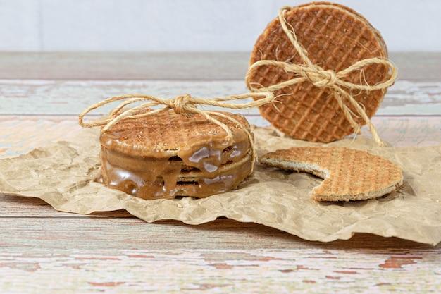 Gros plan d'une pile de stroopwafels avec un arc en sisal, à côté d'un autre biscuit avec une morsure.